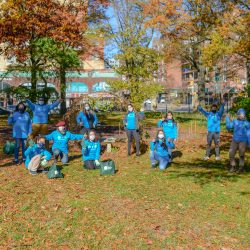 Con Edison volunteers outside waving, wearing masks, wearing blue shirts