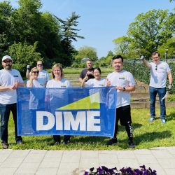 volunteers from DIME community bank holding up DIME banner outside in garden